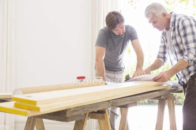 Отец и сын просматривают планы строительства — стоковое фото