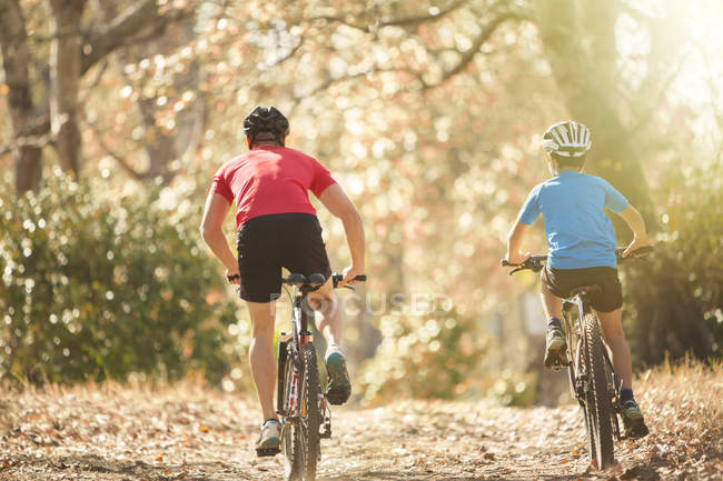 Father and son mountain biking on path in woods — Stock Photo