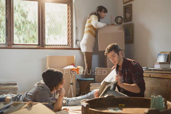 Coinquilini giovani amici adulti disimballaggio scatole studiando in nuovo appartamento — Foto stock