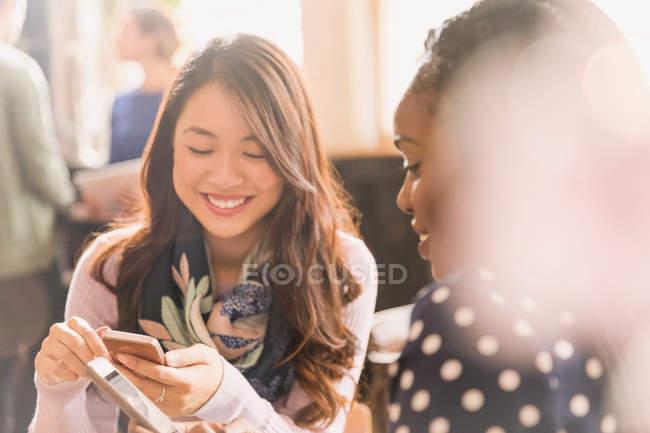 Mensagens de amigos do sexo feminino com telefones celulares no café — Fotografia de Stock