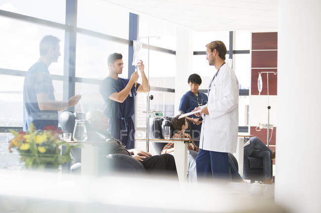 Doctors taking care of patients undergoing medical treatment in outpatient clinic — Stock Photo