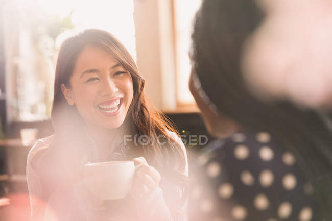 Laughing women talking and drinking coffee in cafe — Stock Photo