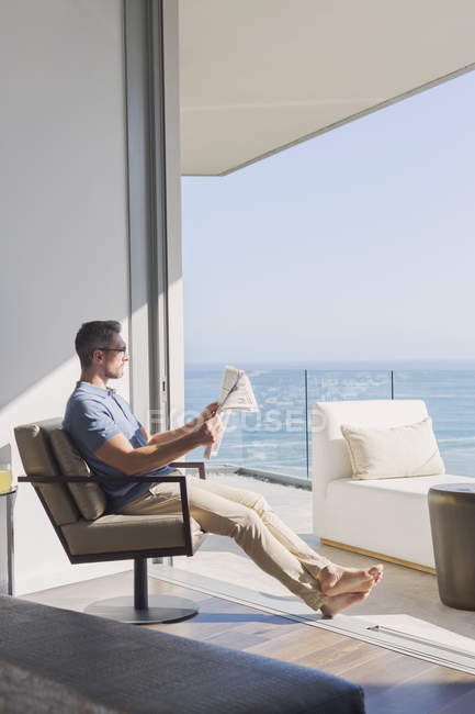 Man relaxing reading newspaper in sunny patio doorway with ocean view — Stock Photo