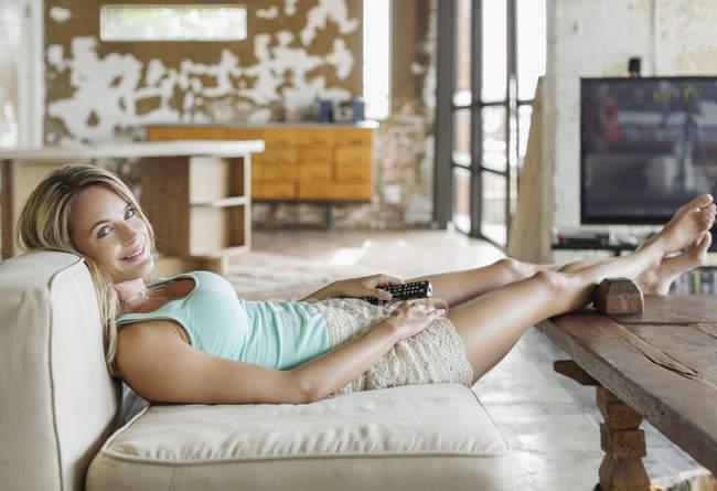 Portrait de femme souriante portant sur canapé avec télécommande — Photo de stock
