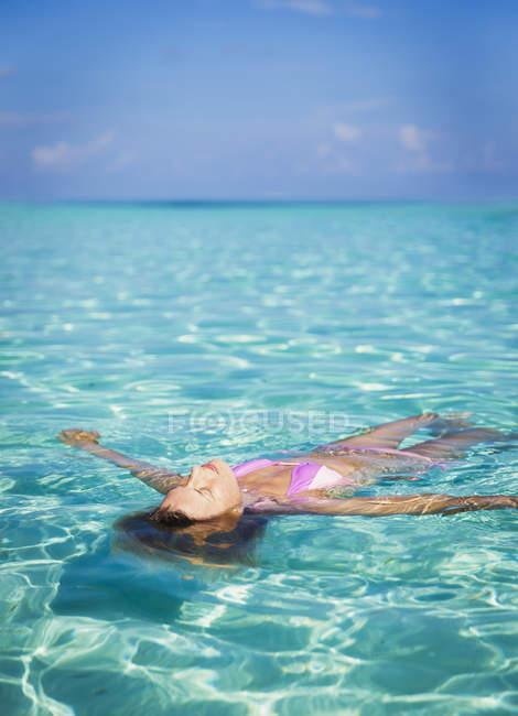 Donna serena che galleggia nell'oceano tropicale — Foto stock