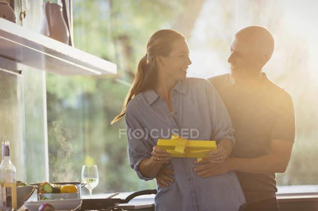 Sonriente esposo sorprende con el regalo en la soleada cocina - foto de stock