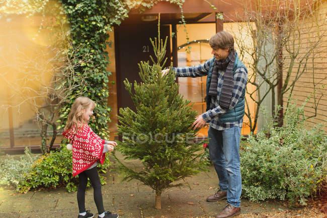 Père et fille avec arbre de Noël en dehors de la maison — Photo de stock