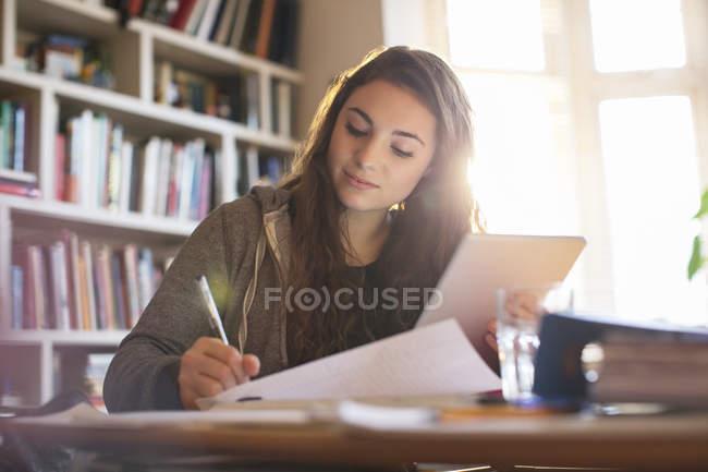 Девочка-подросток с цифровым планшетом делает домашнее задание за столом — стоковое фото