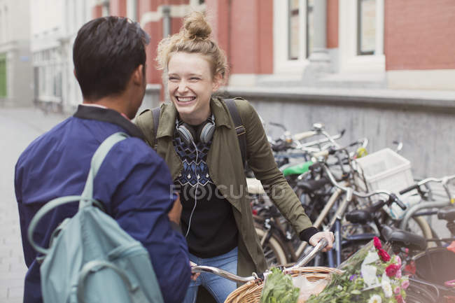 Young man and woman with bicycle laughing on city street — Stock Photo