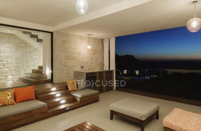 Luxury living room overlooking ocean at night — Stock Photo