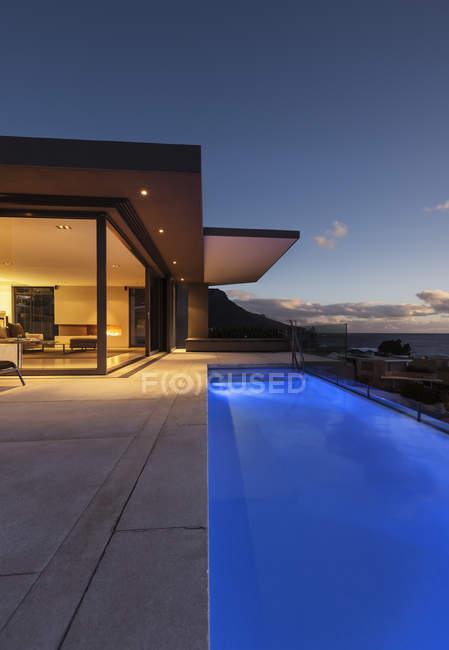 Синий бассейн у витрины современного роскошного дома. — стоковое фото