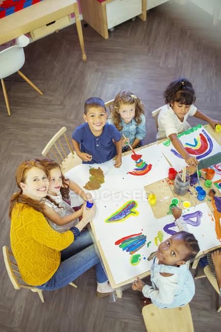 Étudiants et professeur de peinture dans la salle de classe — Photo de stock