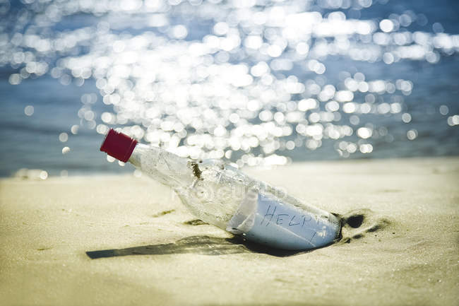 Message in bottle on beach against water — Stock Photo