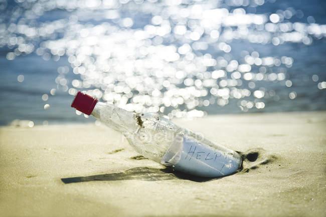 Mensaje en botella en playa contra agua - foto de stock