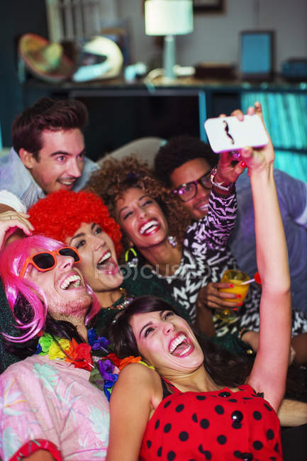 Friends taking self-portrait with camera phone at party — Stock Photo