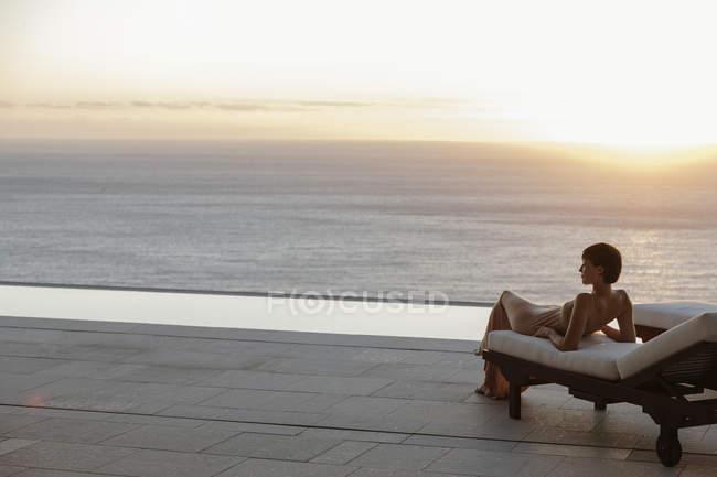 Mujer en vestido que pone en la silla de salón en el patio con vistas al océano al atardecer - foto de stock