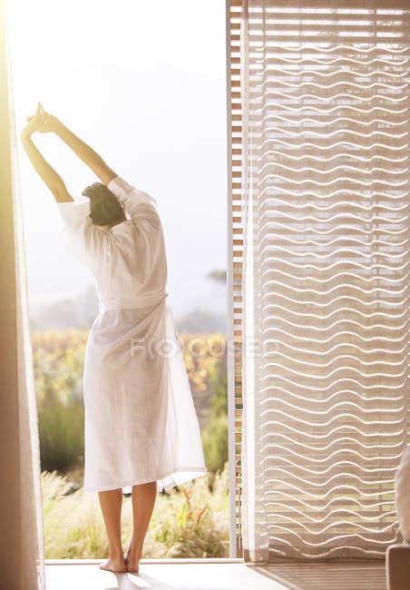 Donna in accappatoio che si estende con le braccia sopra la porta del patio soleggiato — Foto stock