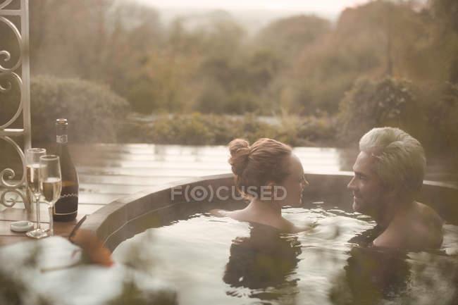 Pareja hablando en remojo en bañera de hidromasaje con champán en el patio de otoño - foto de stock