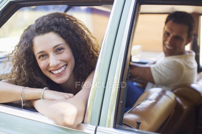 Mujer relajante en la puerta de coche en coche - foto de stock