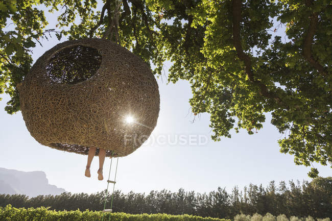 Woman dangling feet from nest tree house — Stock Photo