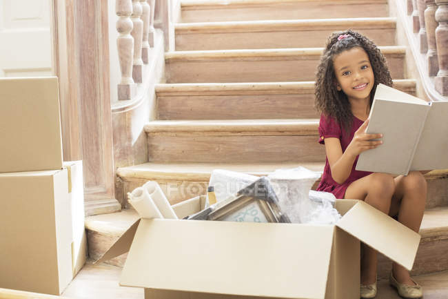 Young girl reading while sitting on stairs — Stock Photo