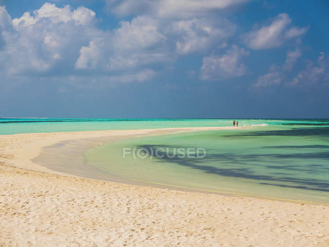 People in distance walking on tropical beach, Maldives — Stock Photo