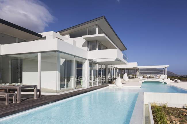 Sonnige, ruhige moderne Luxus nach Hause Schaufenster außen mit Swimming pool — Stockfoto
