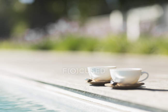 Cappuccino cups at poolside — Stock Photo