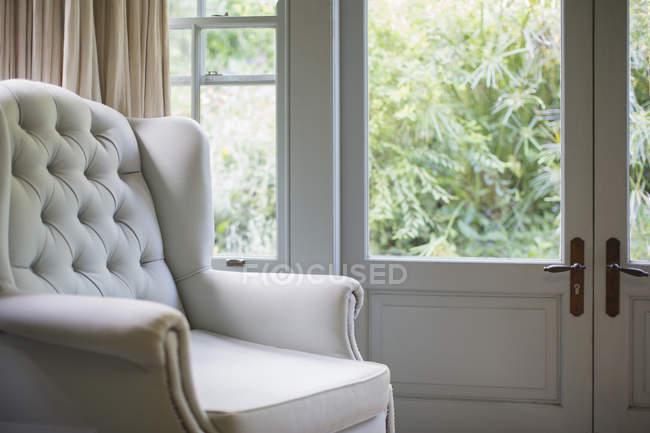 Тафтинговые выступающий кресло около окна — стоковое фото