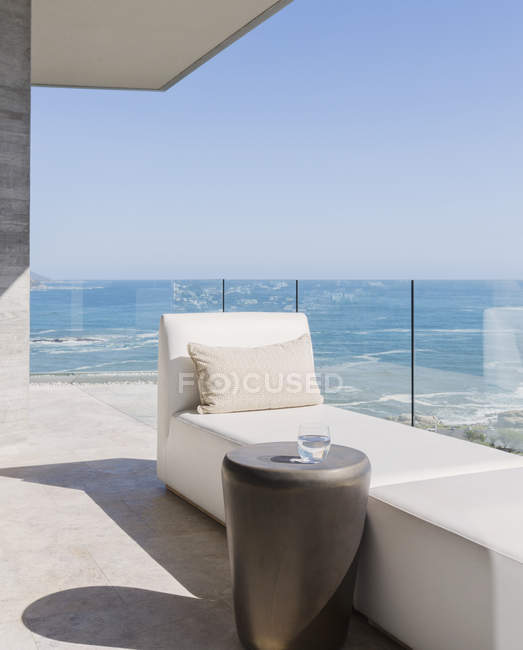 Chaise lounge and water glass on sunny luxury balcony with ocean view — Stock Photo