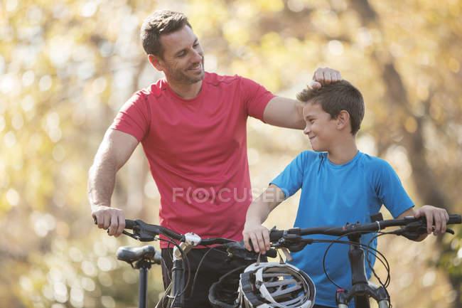 Padre e hijo cariñosos con bicicletas de montaña al aire libre - foto de stock