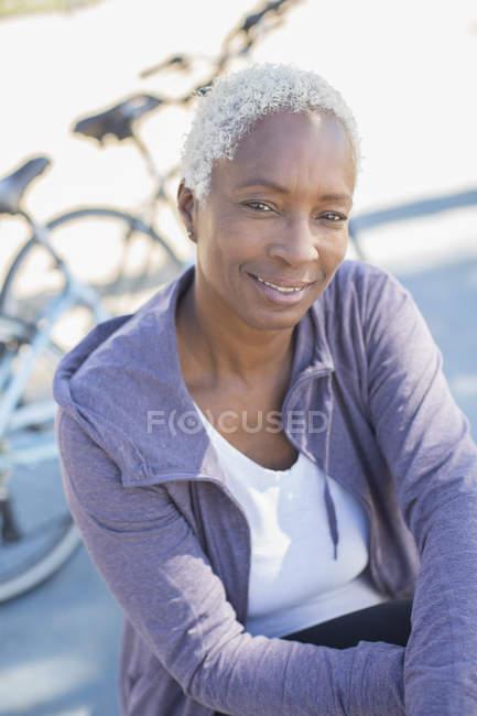 Retrato de mulher sorridente perto de bicicleta — Fotografia de Stock