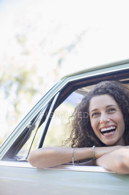 Happy beautiful woman relaxing on car door during car ride — Stock Photo