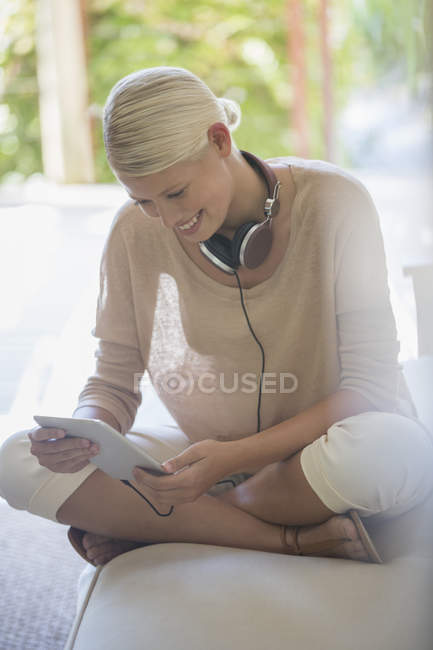 Woman using digital tablet on sofa — Stock Photo