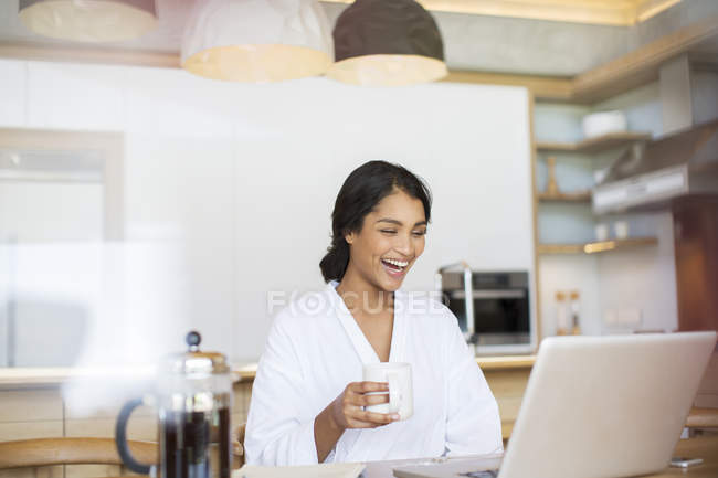 Laughing woman in bathrobe drinking coffee and using laptop — Stock Photo
