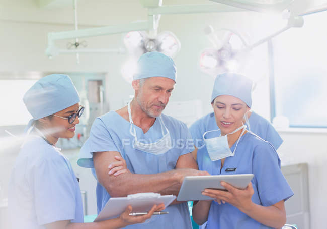 Surgeons and nurse using clipboard and digital tablet in operating room — Stock Photo
