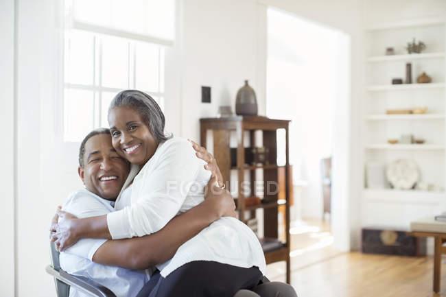 Счастливая пожилая пара обнимается в гостиной — стоковое фото