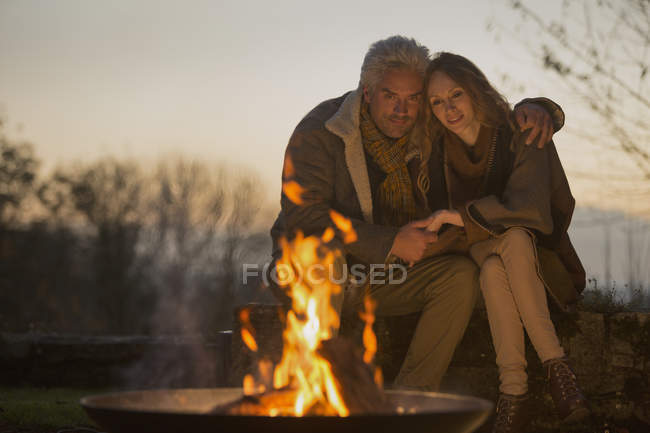 Affectionate serene couple enjoying autumn campfire — Stock Photo