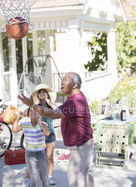 Grandfather and granddaughters playing basketball — Stock Photo