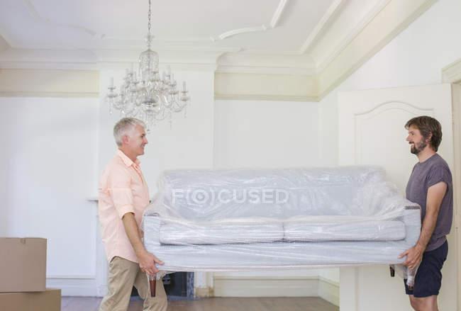 Padre e hijo llevando sofá al espacio vital - foto de stock