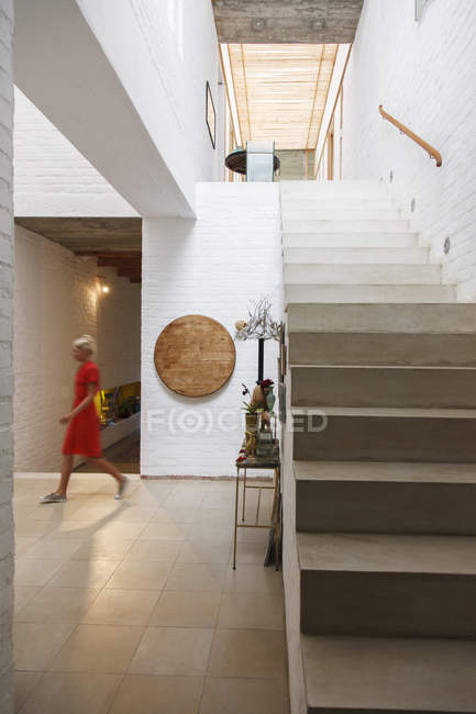 Woman walking by doorway in modern house — Stock Photo