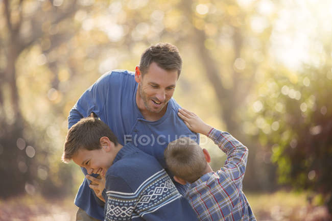 Playful father and sons rough housing outdoors — Stock Photo