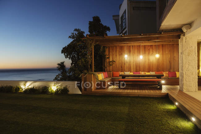 Illuminated patio at night against ocean — Stock Photo