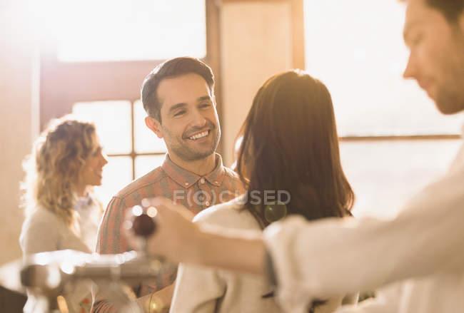 Улыбаясь кавказских человек, разговаривать с женщиной в баре — стоковое фото