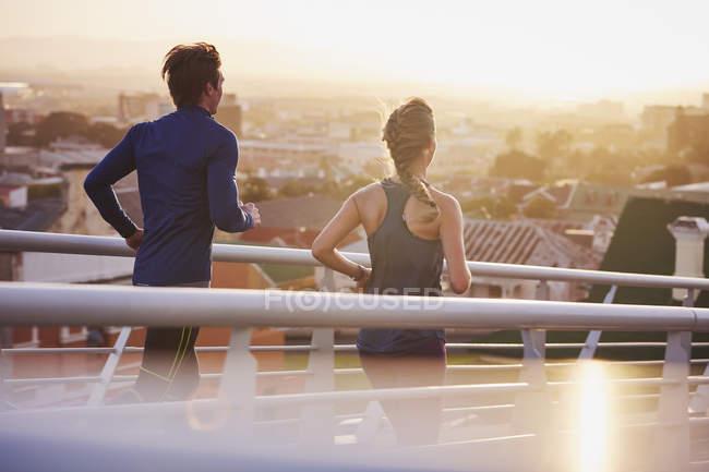 Пара бегунов, бегущая по мосту с видом на город — стоковое фото