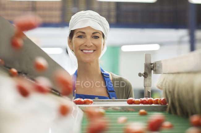 Portrait of smiling worker examining tomatoes at conveyor belt in food processing plant — Stock Photo