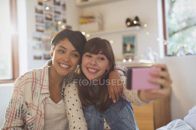 Enthusiastic young women friends taking selfie with camera phone — Stock Photo