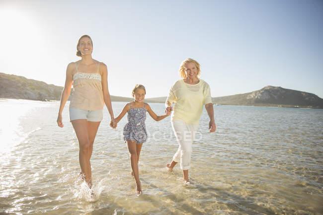 Tre generazioni di donne che camminano sulle onde — Foto stock