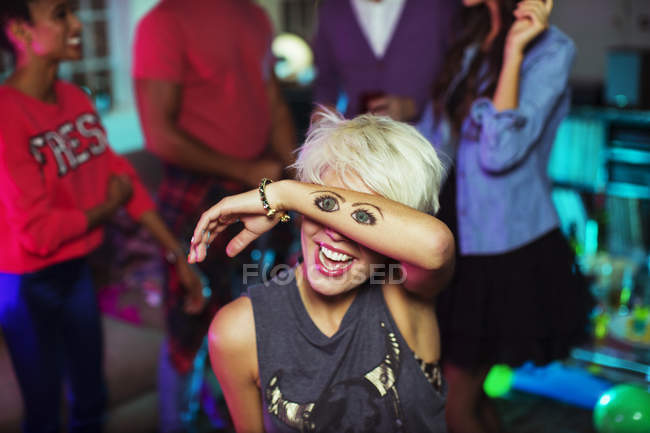 Donna che tiene il tatuaggio degli occhi sul viso — Foto stock