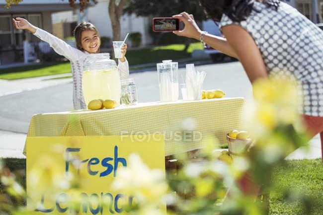 Мать фотографирует дочь на стенде с лимонадом — стоковое фото